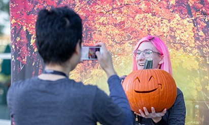 taking a picture with a pumpkin