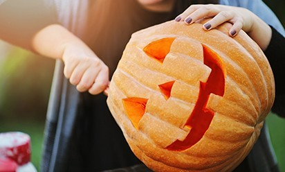 A pumpkin being carved into a jack-o-lantern by a student