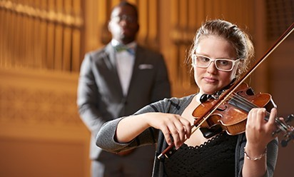 A young woman plays the violin on the stage at Pease.