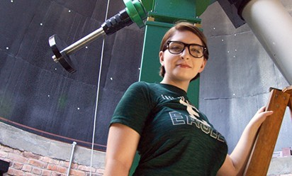 A female student wearing an Eastern t-shirt stands by the big telescope at Sherzer Observatory.