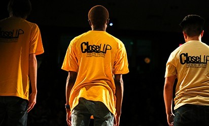 Close-Up Theatre performers on stage wearing yellow Close-Up t-shirts.