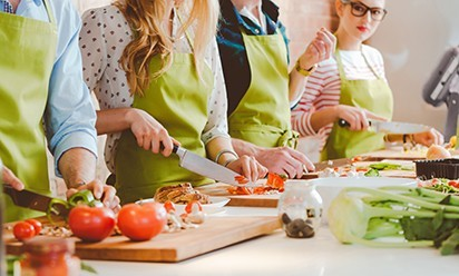 A group of people in a cooking class with green aprons