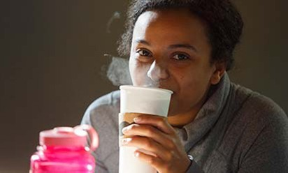 A student is sipping a cup of hot coffee.