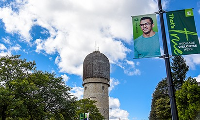 The Ypsilanti Water Tower and a banner featuring EMU international student on a sunny day.