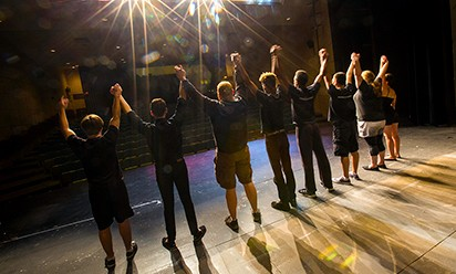 A group of EMU Theatre students hold hands and take a bow in a view from behind them on stage.