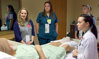 A team of CHHS graduate students gather around the hospital bed of an actor simulating a patient with various health problems.