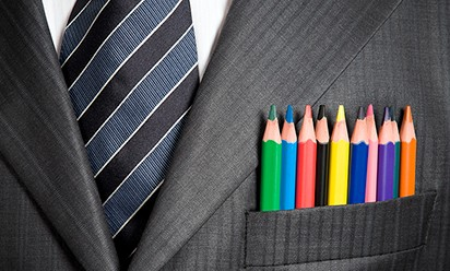 A close up of a suit jacket with many colored pencils in the chest pocket.