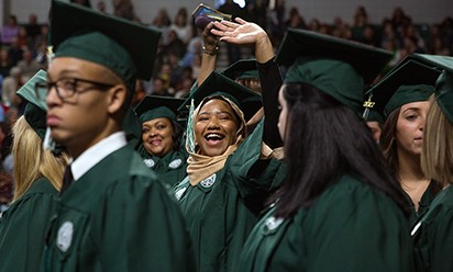 A grad at commencement waves to someone in the crowd at the Convocation Center.