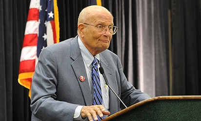 John Dingell speaking at the podium at Eastern Michigan University.