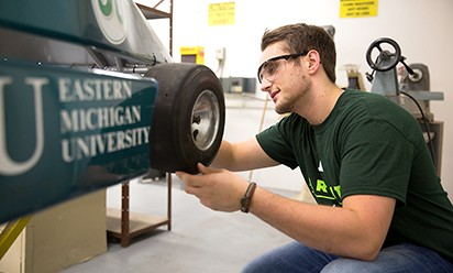 An EMU student working on a vehicle in a COT classroom.