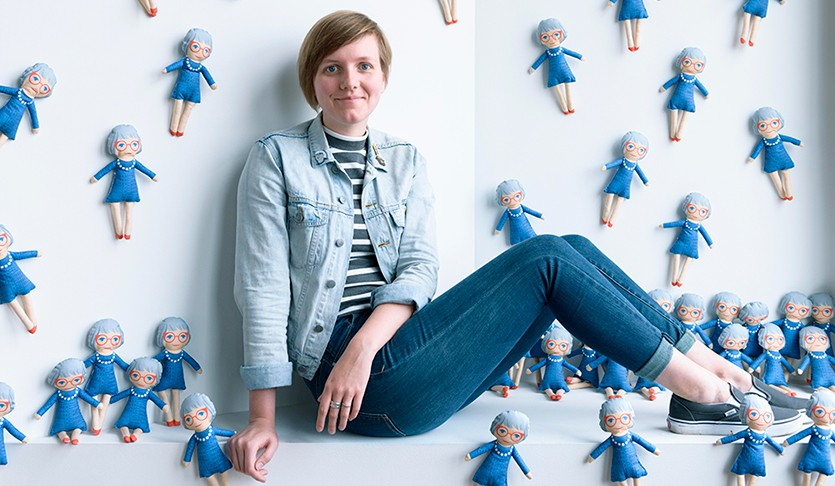 Sarah Marsom poses with her handmade Jane Jacobs dolls.