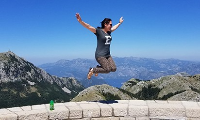 Silvija Marniković wearing EMU shirt jumps at a scenic location in Montenegro