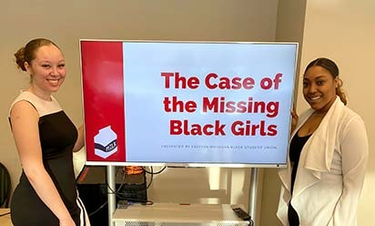 "Kyra Mitchell and Kiera Osborn with ""The Case of Missing Black Girls"" sign"