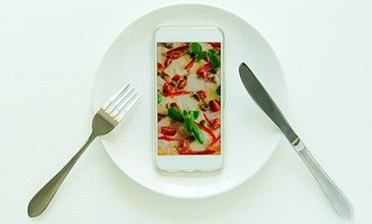 Photo illustration of table setting and phone with food showing on screen