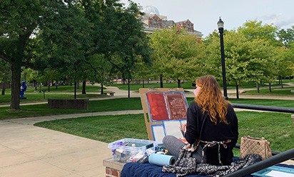 Art student painting outside on campus