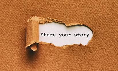 "Orange paper peeling back to reveal the words ""share your story."""