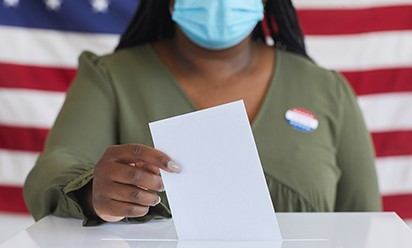 A woman wearing a mask while putting her ballot in a voting box.
