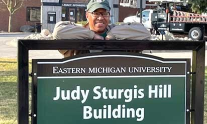 kurt hill leaning on sign that reads judy sturgis hill