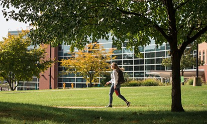 A student walking on campus by the Student Center in the fall