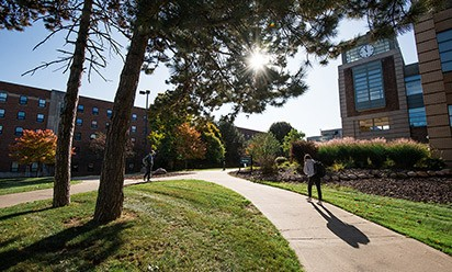 Students walking on campus by Halle Library on a sunny day