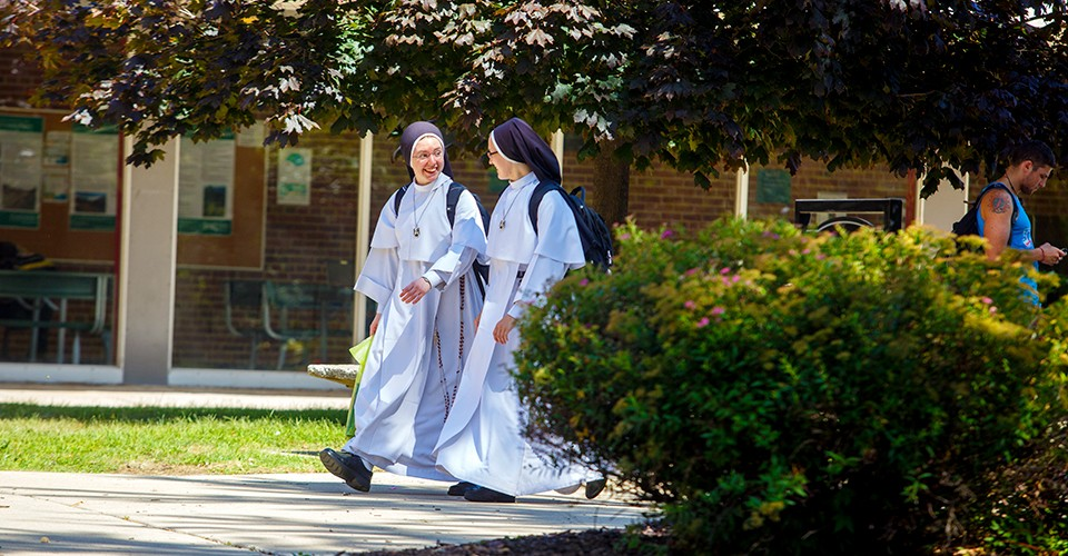 Two Dominican Sisters of Mary nuns talking as they walk across the EMU campus.