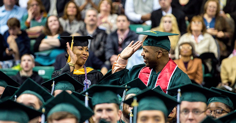 Graduates at commencement ceremony give each other a high-five.