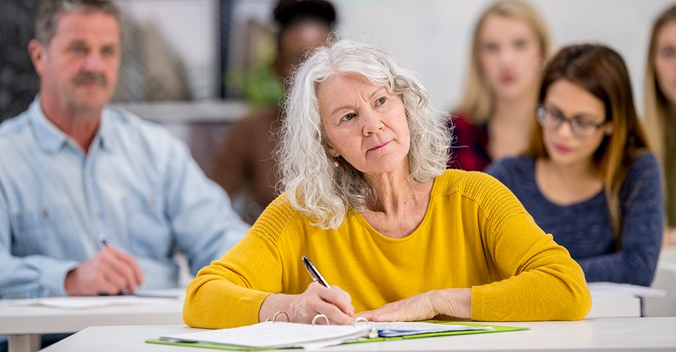 A middle-aged woman takes notes in the classroom.