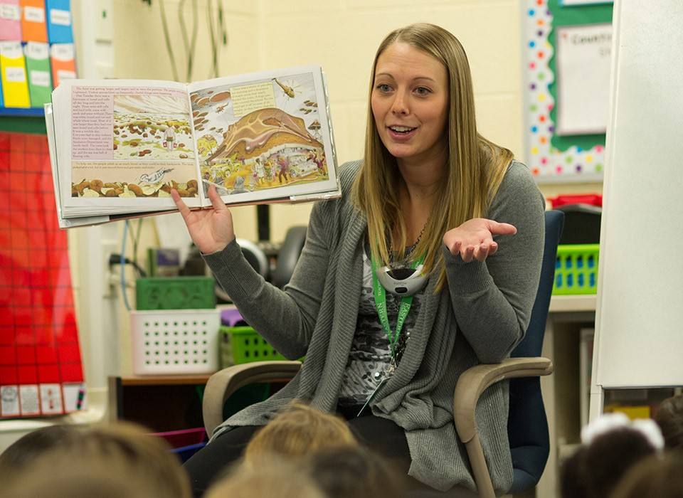 A student teacher reads a book to young pupils.