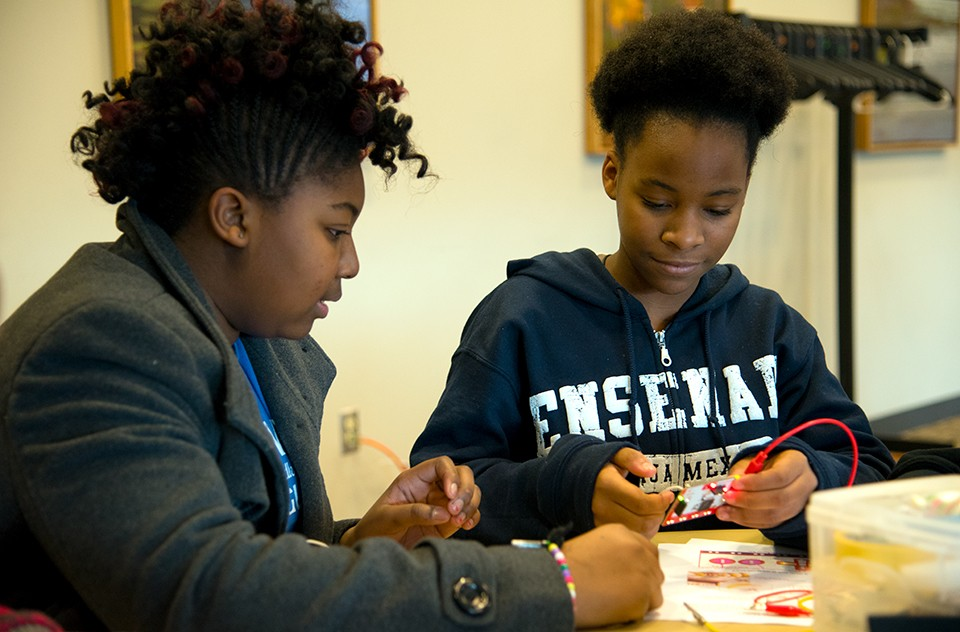 Two middle-school girls work on a project together at Digital Divas.