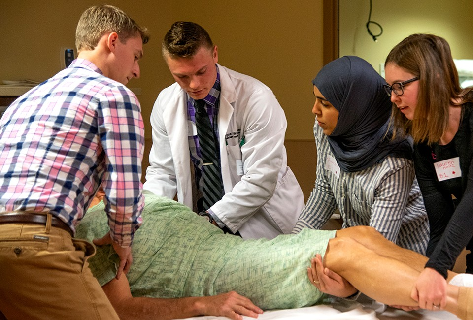 A team of students in various health-related fields gather around the hospital bed of a mock patient at the Interprofessional Education Day.