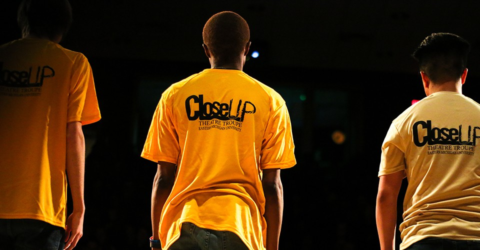 Students on stage with t-shirts that say Close-Up Theatre on the back.