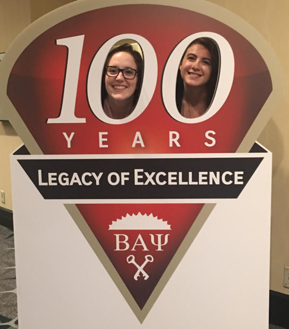 Two members of Beta Alpha Psi poke their heads through a poster at the annual meeting in Washington, D.C.