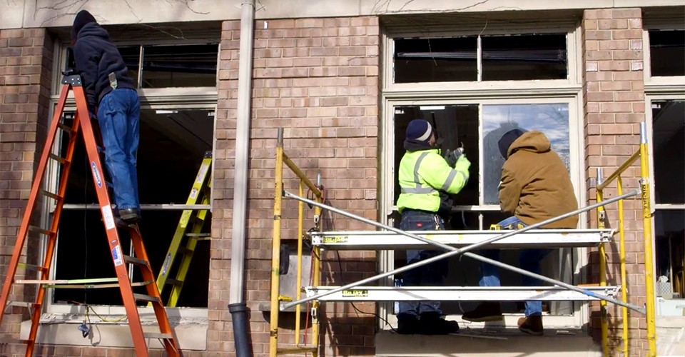 Workers install new high tech glass in some buildings around campus.