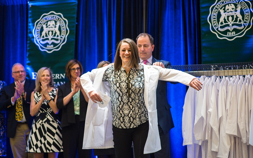 A student in EMU's PA Program puts on a lab coat in a ceremony.