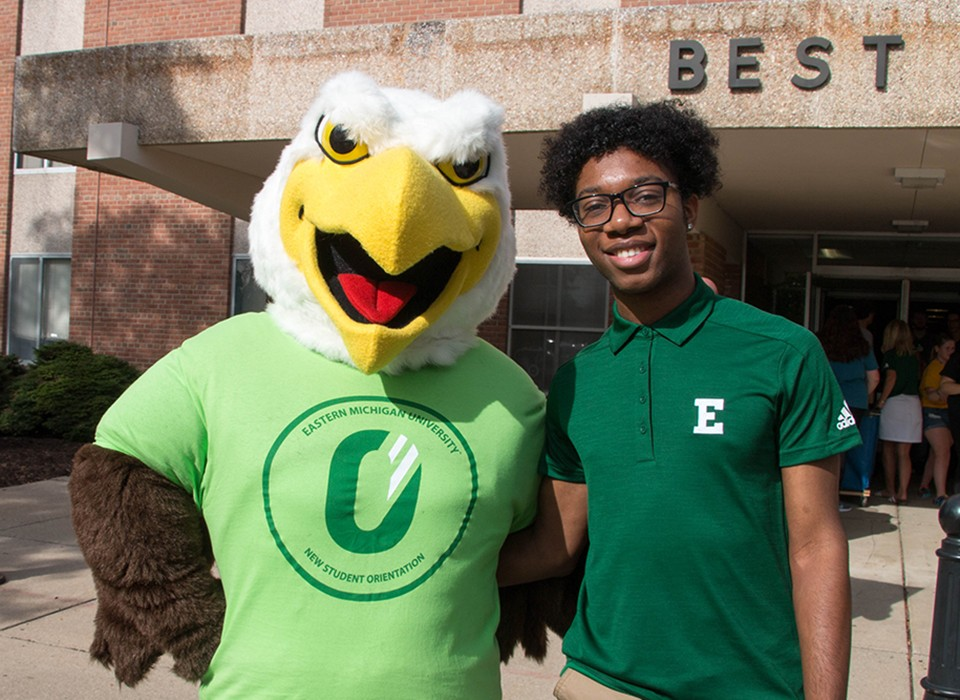 Swoop and EMU student outside of the dorm