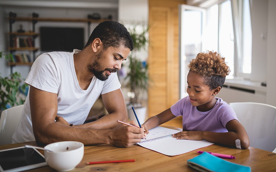 A father and daughter home schooling