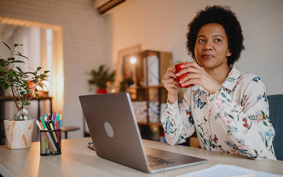 A woman working from home with laptop and coffee
