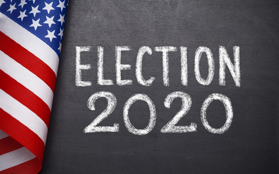 "An American flag and a chalkboard with ""Election 2020"" written on it"