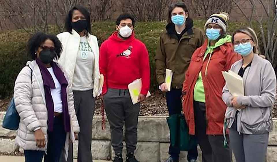 six people outside in a row with masks on