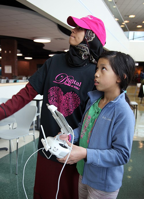 A middle-school student and an instructor work the controls of a drone at Digital Divas 2018.