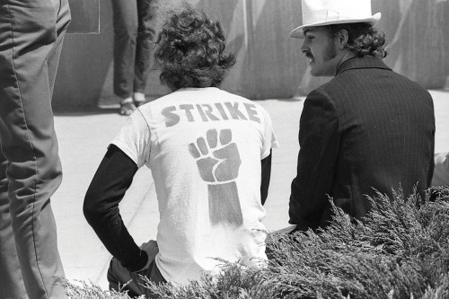 Archival photo of EMU students in 1969, one wearing a t-shirt with protest graphic.